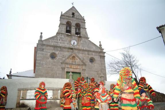 Caretos junto à Igreja de Nossa Senhora da Purificação de Podence foto exposta no site oficial do Grupo de Caretos de Podence